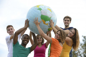 Group of young people holding a globe planet earth